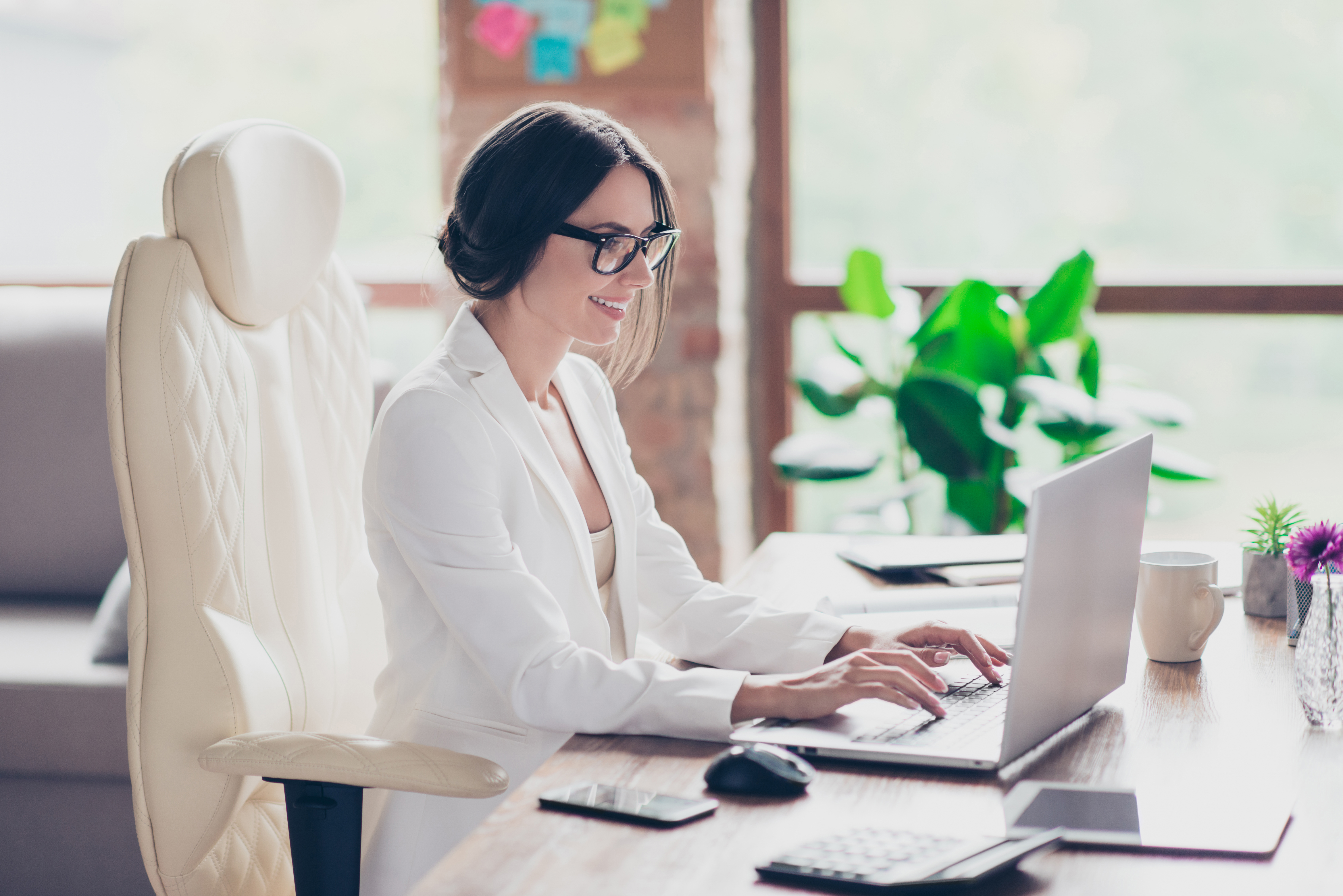 Joyful cute beautiful attractive glad clever manager is sitting at the table in her bright well-equiped office and chatting with colleagues via the internet
